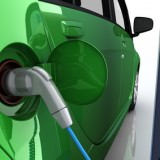 Grünes Elektroauto an der Ladestation einer Tankstelle mit Stromkabel